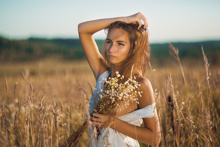 Sensual young girl with slim body standing in field of tall grass in unbuttoned sleeveless jean sundress and covering her naked breasts by bouquet 免版税图像