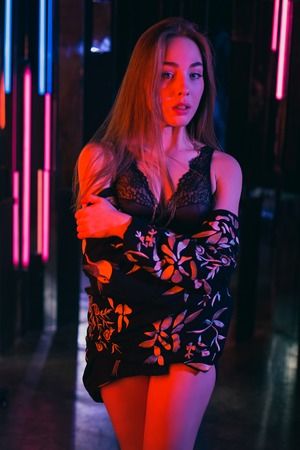 Sexy young woman standing and posing in sexy lingerie in a room of neon lights Reklamní fotografie