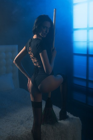 Sensual young woman in a sexy black lingerie as a witch costume, stending with a broom getting ready to halloween party in a room full of haze and moon light beam trough the window.