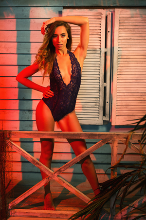 Beautiful young woman with an attractive athletic figure and big natural breasts standing in a purple bodysuit and posing at a beach house near ocean side at sunset.