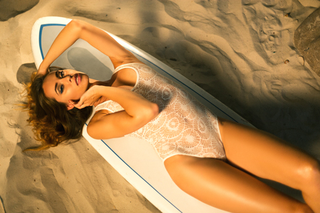 Attractive young woman with an athletic figure and long beautiful hair posing lying in a white bodysuit on a surfboard on the beach near the ocean.