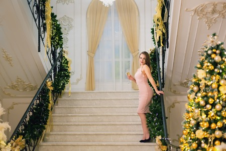 Young beautiful woman in pink elegant evening dress staying and posing on stairways leaning on handrail in a chic hall with christmas tree and presents on a new year eve.