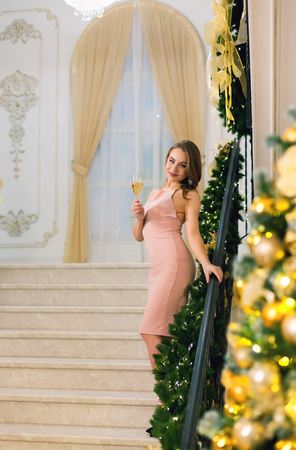 Beautiful young woman in pink elegant evening dress staying and posing on stairways leaning on handrail in a chic hall with christmas tree and presents on a new year eve. Reklamní fotografie