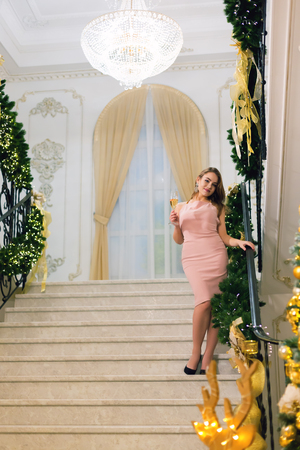 Attractive young woman in pink elegant evening dress staying and posing on stairways leaning on handrail in a chic hall with christmas tree and presents on a new year eve.