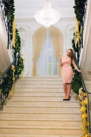 Sensual young woman in pink elegant evening dress staying and posing on stairways leaning on handrail in a chic hall with christmas tree and presents on a new year eve. Imagens