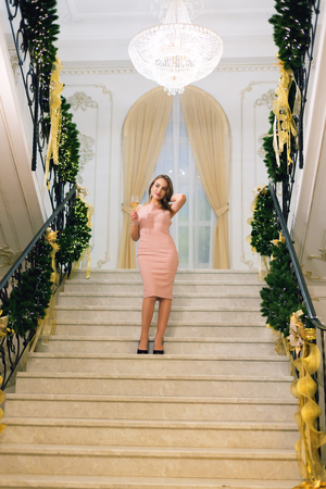 Lovely young woman in pink elegant evening dress staying and posing on stairways leaning on handrail in a chic hall with christmas tree and presents on a new year eve. Reklamní fotografie - 113727263