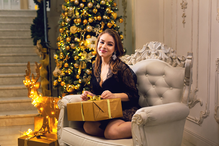 Attractive young woman in black lace peignoir sitting in ampir chair with a Christmas gift in her hands on a new year eve. Stok Fotoğraf
