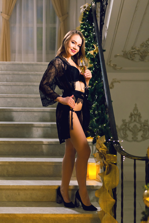 Beautiful young woman in black lace peignoir and black lingerie standing and posing on a stairways with Christmas decoration in a chic hall on a new year eve.