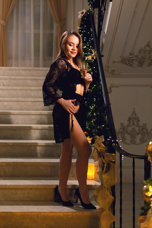 Sensual young woman in black lace peignoir and black lingerie standing and posing on a stairways with Christmas decoration in a chic hall on a new year eve. Reklamní fotografie
