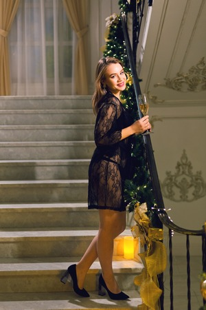 Sensual young woman in a black lace peignoir standing and posing on a stairways with Christmas decoration in a chic hall on a new year eve.