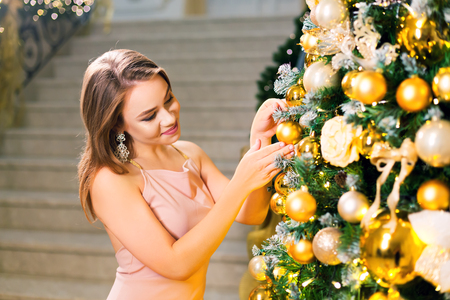 Beautiful young woman in a pink elegant evening dress staying in a chic hall and dressing up a christmas tree with yellow ball on a new year eve. Reklamní fotografie - 113727294