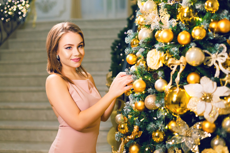 Attractive young woman in a pink elegant evening dress staying in a chic hall and dressing up a christmas tree with yellow ball looking in camera, on a new year eve. Stok Fotoğraf