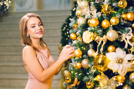 Cute young woman in a pink elegant evening dress staying in a chic hall and dressing up a christmas tree with yellow ball on a new year eve.