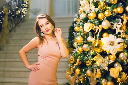 Beautiful young woman in a pink elegant evening dress staying in a chic hall and posing near xmas tree on a new year eve. Stok Fotoğraf