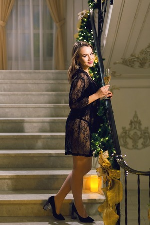 Attractive woman in black peignoir standing and posing on a stairways with Christmas decoration in a chic hall on a new year eve Reklamní fotografie