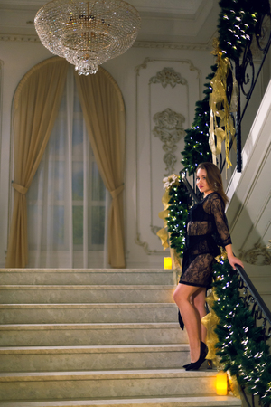 Young woman in black peignoir standing and posing on a stairways with Christmas decoration in a chic hall on a new year eve