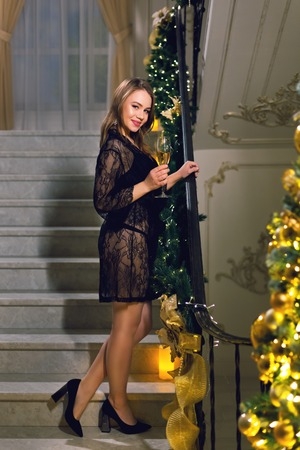 Beautiful young woman in black peignoir standing and posing on a stairways with Christmas decoration in a chic hall on a new year eve