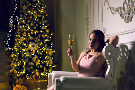 Attractive young woman is sitting in a dark chic hall with a Christmas tree dressed up in a garland in ampir chair with a glass of champagne in her hands enjoying new year holidays.