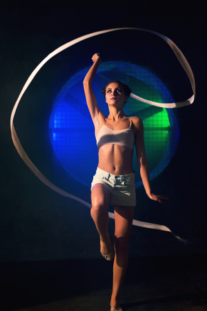 Beautiful young gymnast woman training with a gymnastics tape against the black wall with a big fan lit with blue and green neon light Stok Fotoğraf