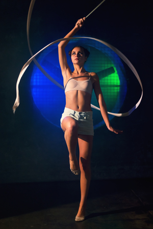 Attractive young gymnast woman training with a gymnastics tape against the black wall with a big fan lit with blue and green neon light Stok Fotoğraf