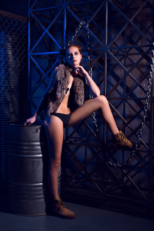 Beautiful young sexy woman posing topless or nude in fur jacket in steampunk style scene leaning on metal barrel and with a leg on metall fence on dark moody background. Reklamní fotografie - 113727606