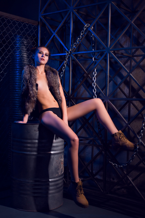Sultry beauty young sexy woman posing topless or nude in fur jacket in steampunk style scene sitting on metal barrel and with a leg on metall fence on dark moody background.
