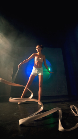 Long shot of an young gymnast woman with a slim sport body training with a gymnastics tape against the black wall with a big fan lit with blue and green neon light. Reklamní fotografie