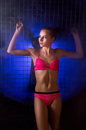 Attractive young athletic woman standing and posing in a pink lingerie bra and panties against the black wall with a big fan lit with blue neon light.