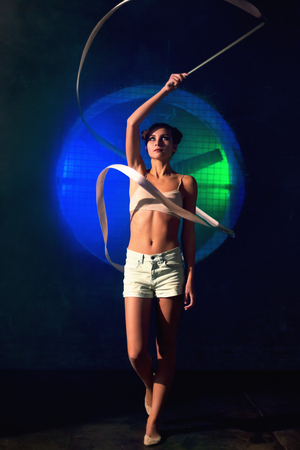 Young gymnast woman training with a gymnastics tape against the black wall with a big fan lit with blue and green neon light