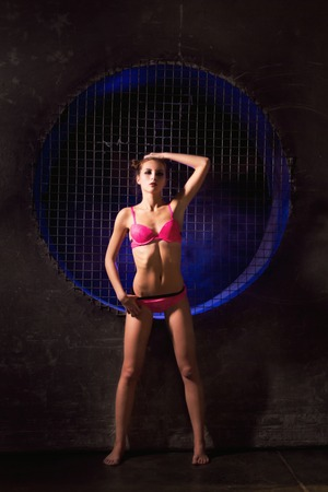 Sultry beauty young athletic woman standing and posing in a pink lingerie bra and panties against the black wall with a big fan lit with blue neon light.