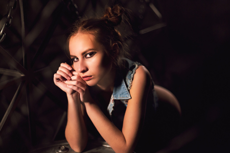 Beautiful young woman posing naked or nude in a jeans jacket leaning on metal tank on dark moody background.