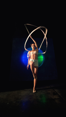 Long shot of an attractive young gymnast woman with a slim sport body training with a gymnastics tape against the black wall with a big fan lit with blue and green neon light.