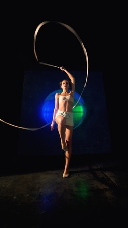 Long shot of a beautiful young gymnast woman with a slim sport body training with a gymnastics tape against the black wall with a big fan lit with blue and green neon light.
