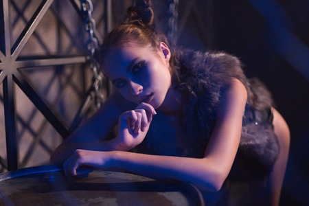 Sensual young woman posing topless or nude in fur jacket in steampunk style scene leaning on metal barrel on a dark moody background. Reklamní fotografie