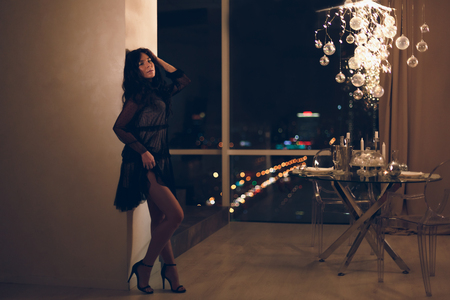 Beautiful young woman in black lace cocktail dress leaning on a wall in hotel room with owesome view on night city from a window and served dining table.