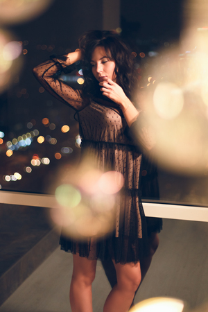 Sensual young woman in black lace cocktail dress standing in alluring pose in front of window with owesome view on a night city. Reklamní fotografie - 113727773