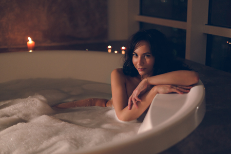 Attractive young woman sitting relaxing in a bath with candles on a dark background in luxury hotel room Stok Fotoğraf