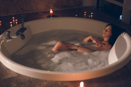 Gorgeous young woman sitting enjoying herself in a bath with a foam and candles on a dark background in luxury hotel room and flirting looking in camera. Reklamní fotografie - 113727990