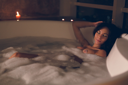 Attractive young woman sitting enjoying herself in a bath with a foam and candles on a dark background in luxury hotel room and flirting looking in camera.