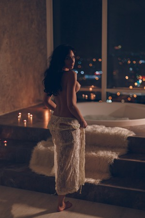 Attractive young woman staying naked or nude with white lace robe on her hips getting ready to take a bath in luxury hotel room at night with awesome city lights view trough big window.