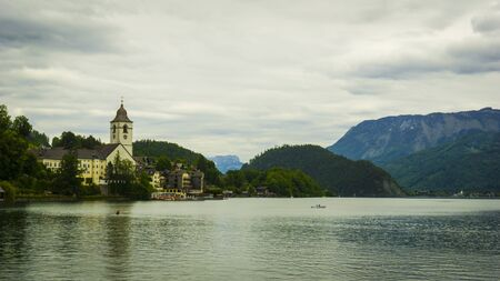 Beautiful Alps landscape with big lake,  green mountains, valley, forest and church on the Coast Stock fotó