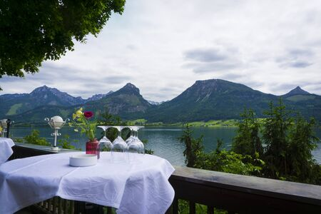 Beautiful Alps landscape with big lake,  green mountains, valley, forest and table with glases of a restauran foreground Stock fotó