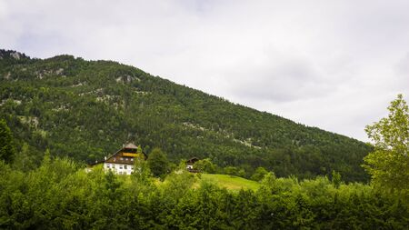 Beautiful Alps landscape with green mountains, valley, cozy hause and forest