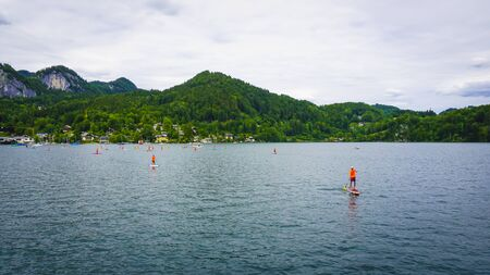 Beautiful Alps landscape with big lake surrounded by green mountains, sailing people on small boats Stock fotó