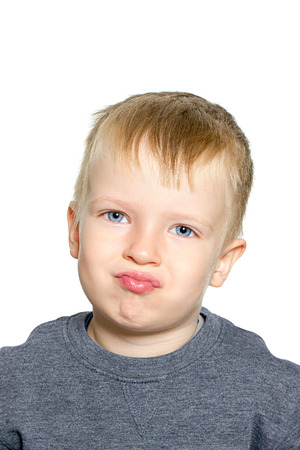 A child of 3 years old grimaces with his face Standard-Bild - 120976643