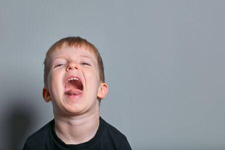 Portrait of a cute little boy who screams. Against a grey background