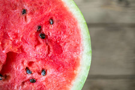 Half of watermelon on wood background. Healthy food for vegan. Top view