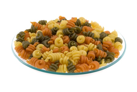 Variety of colorful pasta on plate isolated on white background