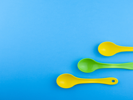 Yellow green plastic spoons on blue background with copyspace for text
