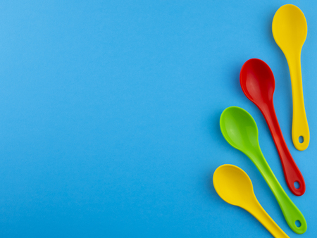 Yellow red green plastic spoons on blue background with copyspace for text Banco de Imagens
